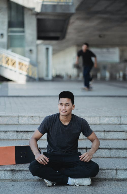 Cheerful Asian man sitting in lotus pose on street stairs