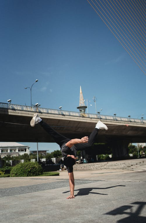 Faceless skilled male dancer performing handstand breakdance movement