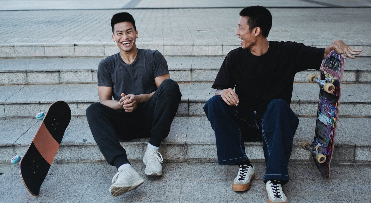 Excited happy Asian skaters resting on stone stairs