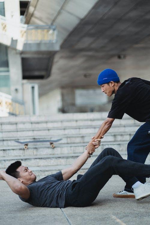 Asian man giving hand to fallen friend