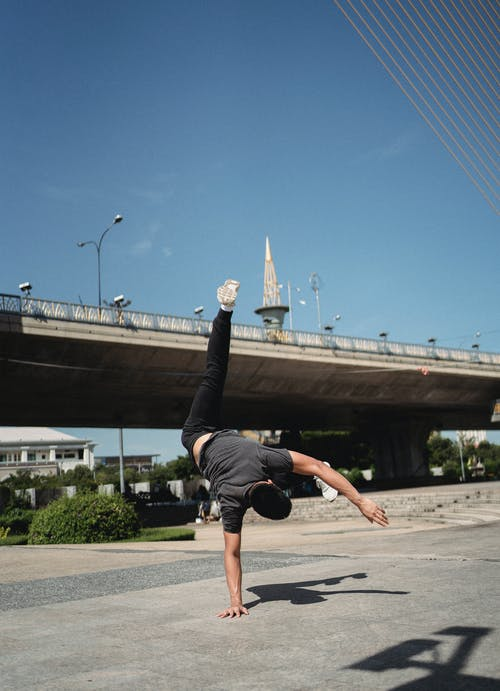 Anonymous man practicing handstand on street