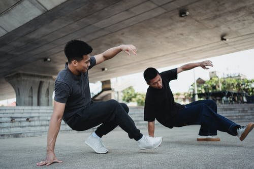 Energetic Asian men performing breakdance under elevated highway