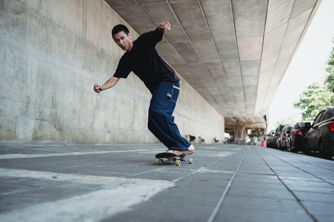 Energetic Asian man skateboarding on paved sidewalk