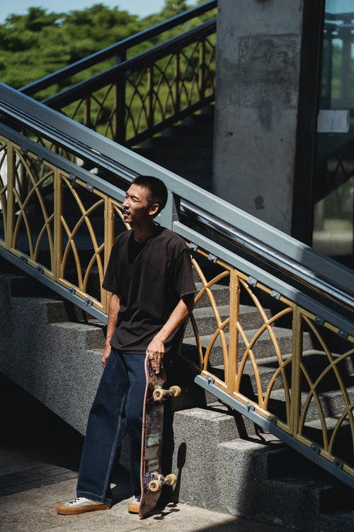Content Asian man standing with skateboard near street staircase