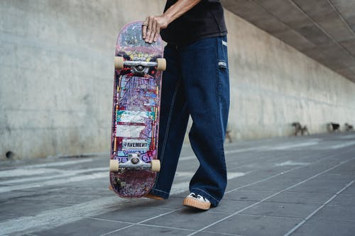Crop unrecognizable male skater in loose pants standing with skateboard standing on paved walkway