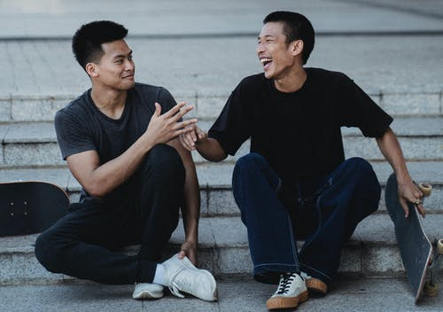 Laughing Asian male skaters resting on street staircase