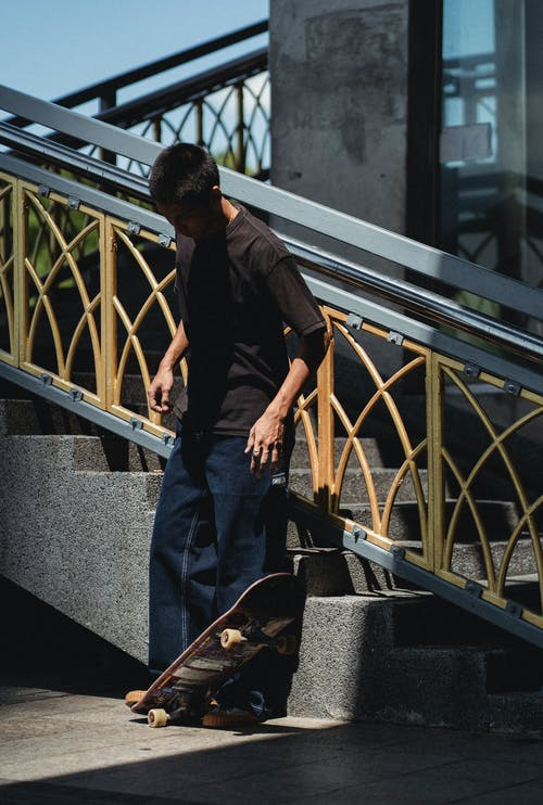 Full body concentrated Asian male wearing street style clothes playing with skateboard while standing near street stairs on sunny weather
