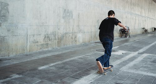 Full body of faceless teenage skater in casual outfit practicing skateboard riding on paved street