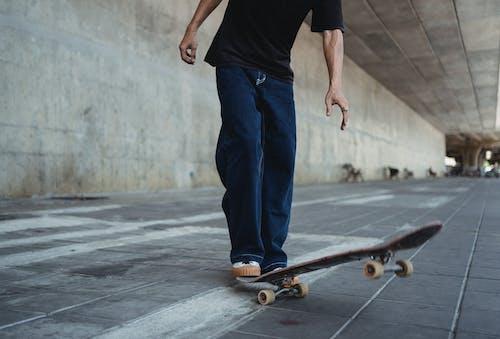 Crop man with skateboard on street