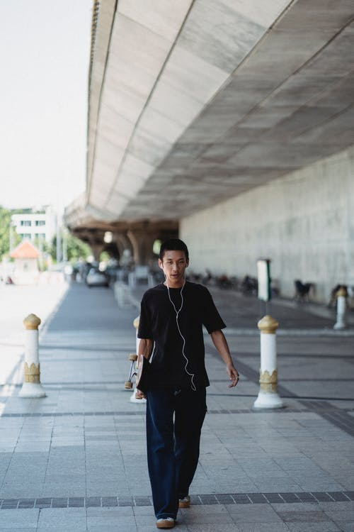Full body of serious male with earphones in casual outfit holding skateboard while walking on sidewalk