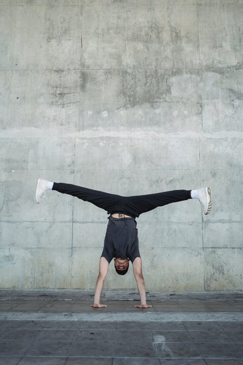 Full body of fit male in sportswear performing handstand while dancing break on pavement
