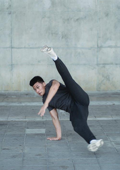 Flexible Asian man breakdancing on pavement