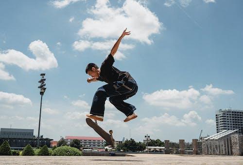 亞洲男子在滑板上執行kickflip