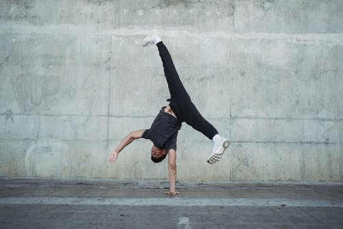 Strong man breakdancing on sidewalk of city
