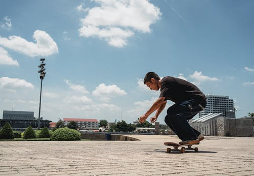 Side view of active male skater riding skateboard on sidewalk of modern city