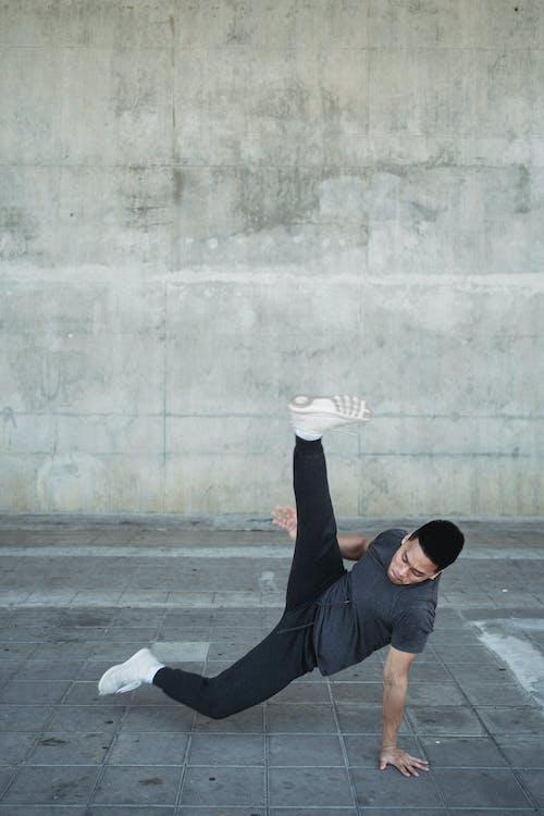 Strong Asian man dancing break on pavement