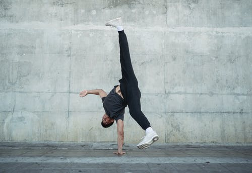 Young man dancing hip hop style on urban landscape