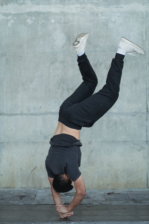 Young sportsman practicing standing on hands on concrete wall background