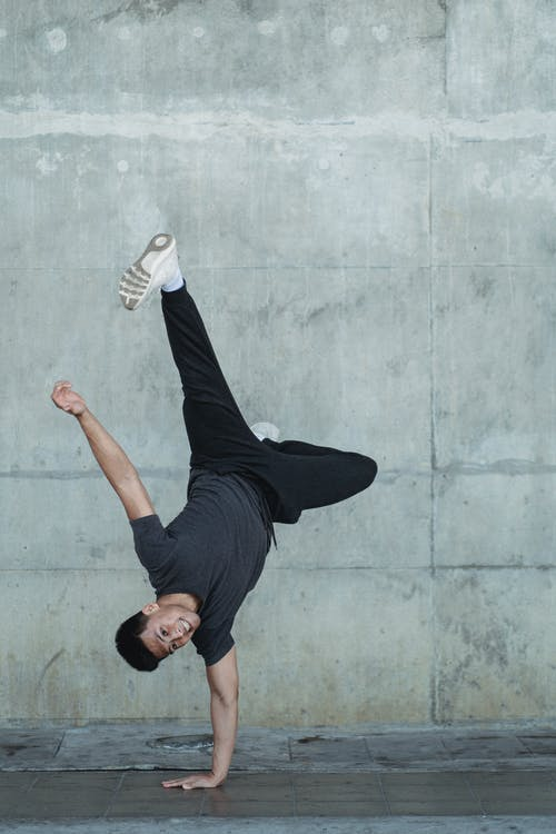 Young man practicing in break dance on gray street