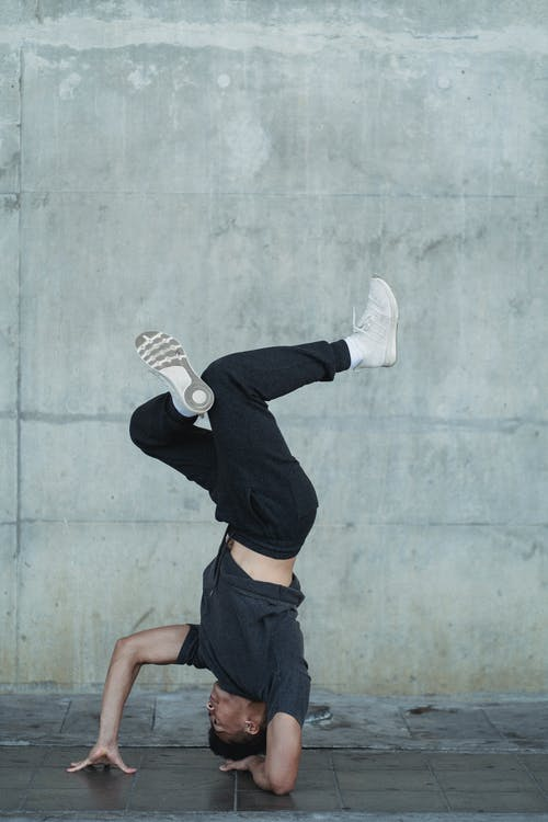 Young guy standing on head during break dance training