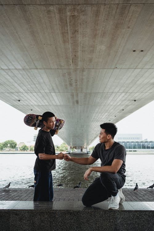 Smiling Asian men giving fist bump on river embankment under bridge