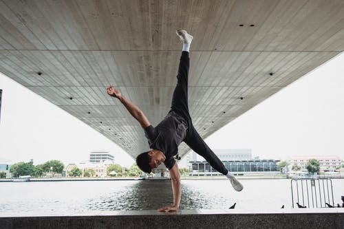 Young man doing handstand on fence of river embankment