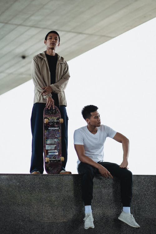 Full body of tranquil Asian men with skateboard standing and looking at camera sitting on steps in daytime