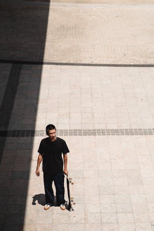 Skater with skateboard standing on street