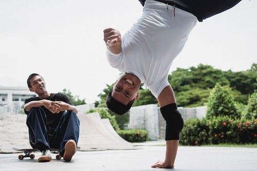 Cheerful men training breakdance in park