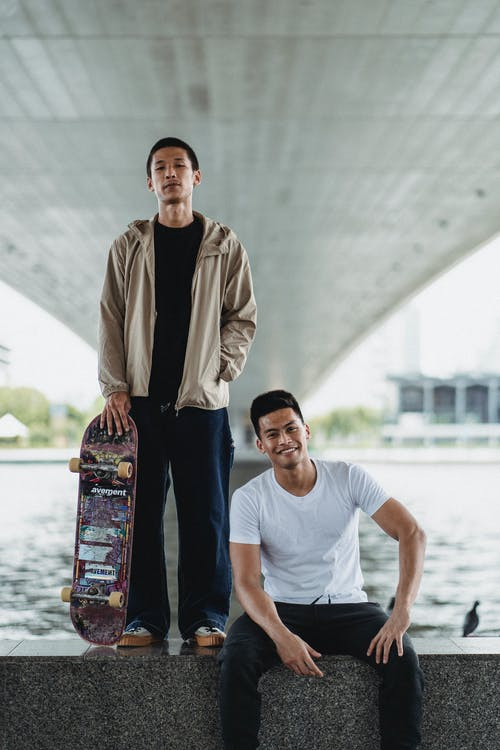 Young men with skateboard on embankment