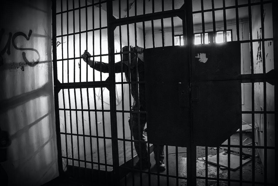Man in Black Jacket Standing Beside Black Metal Gate