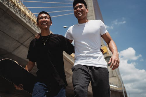 Crop cheerful Asian friends with skateboard walking on street