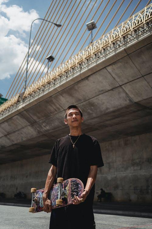 Dreamy ethnic sportsman with skateboard against city bridge
