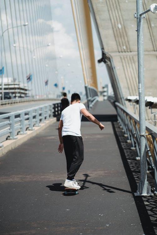 Unrecognizable sportsman skateboarding on bridge in town
