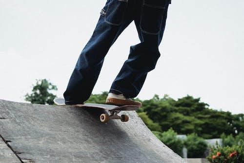 Faceless sportsman skateboarding on ramp in skate park