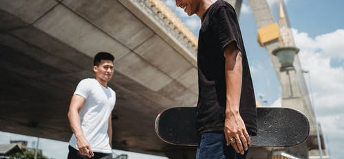 Crop smiling man with skateboard near ethnic friend in town