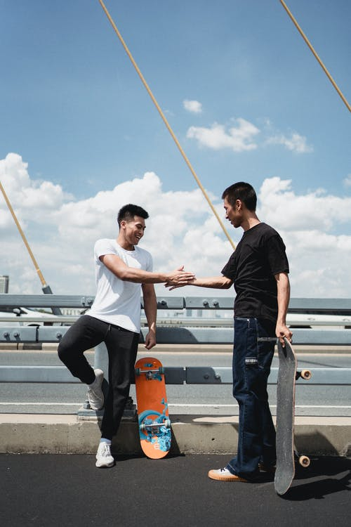 Asian skateboarders greeting each other on suspension bridge