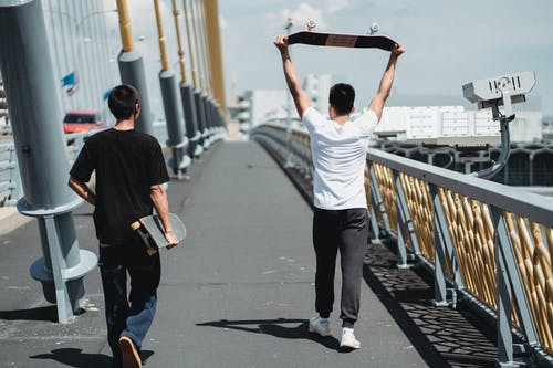 Back view of anonymous male friends with skateboards strolling on fenced bridge in city
