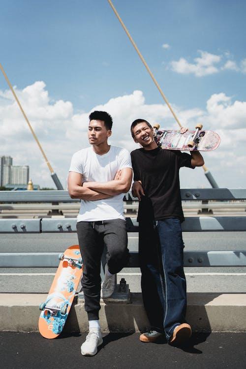 Best Asian friends with skateboards near fence