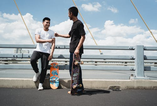 Cheerful Asian partners greeting each other on fenced bridge