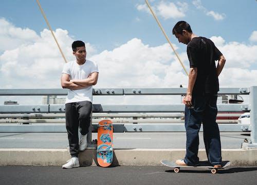 Asian skateboarders on urban bridge in summer