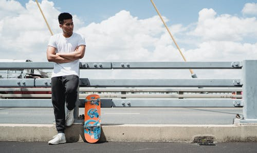 Masculine Asian sportsman with crossed arms near skateboard in town