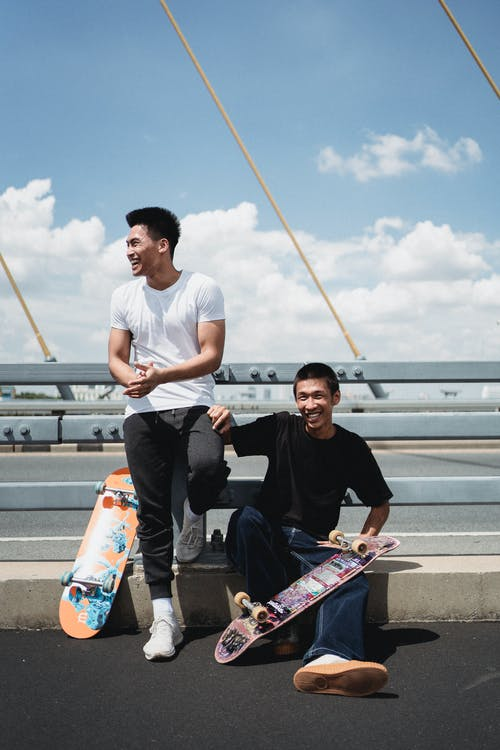 Positive best ethnic friends with skateboards in town