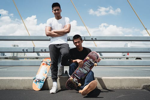 Smiling ethnic male partners with skateboards on bridge pavement