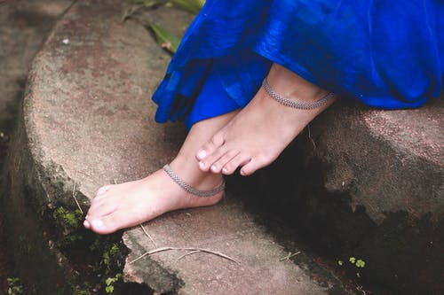 From above of crop anonymous female in blue dress with silver bracelets on feet on shabby wet steps covered with moss