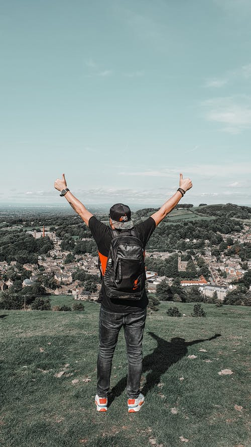 Back view of unrecognizable young male traveler in trendy outfit showing thumbs up gesture while admiring nature standing on green hill on sunny day