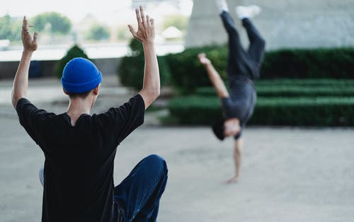 Back view of faceless male in casual clothes instructing friend while performing handstand on city street