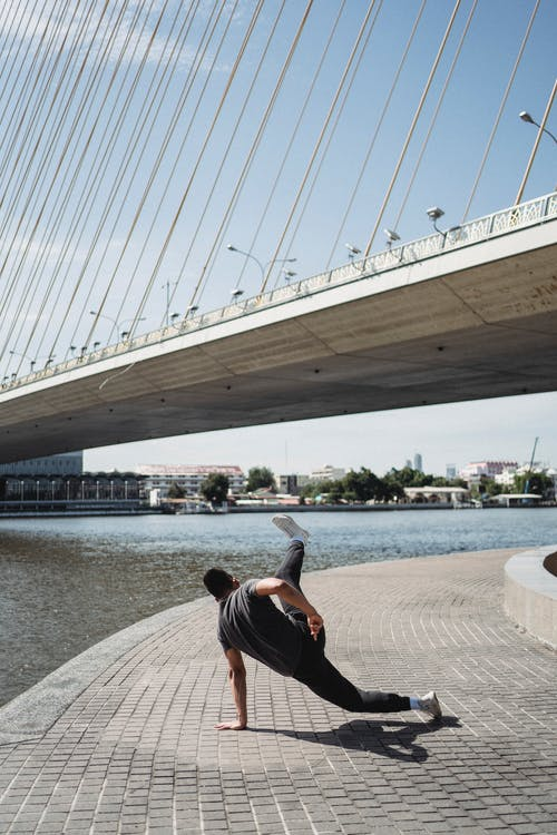 Strong man breakdancing on embankment near river