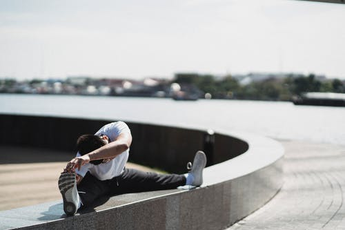 Full body of faceless male athlete in sportswear stretching body while training on city street