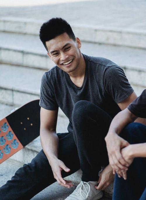 Man in Black Crew Neck T-shirt Sitting On Concrete Steps